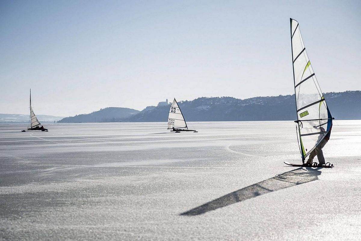 Ice yachts and an ice surfer sliding on the frozen Lake Balaton during a meeting of ice yachts organised by the Balatonfuredi Yacht Club in Balatonfured, Hungary, on Jan 2017.