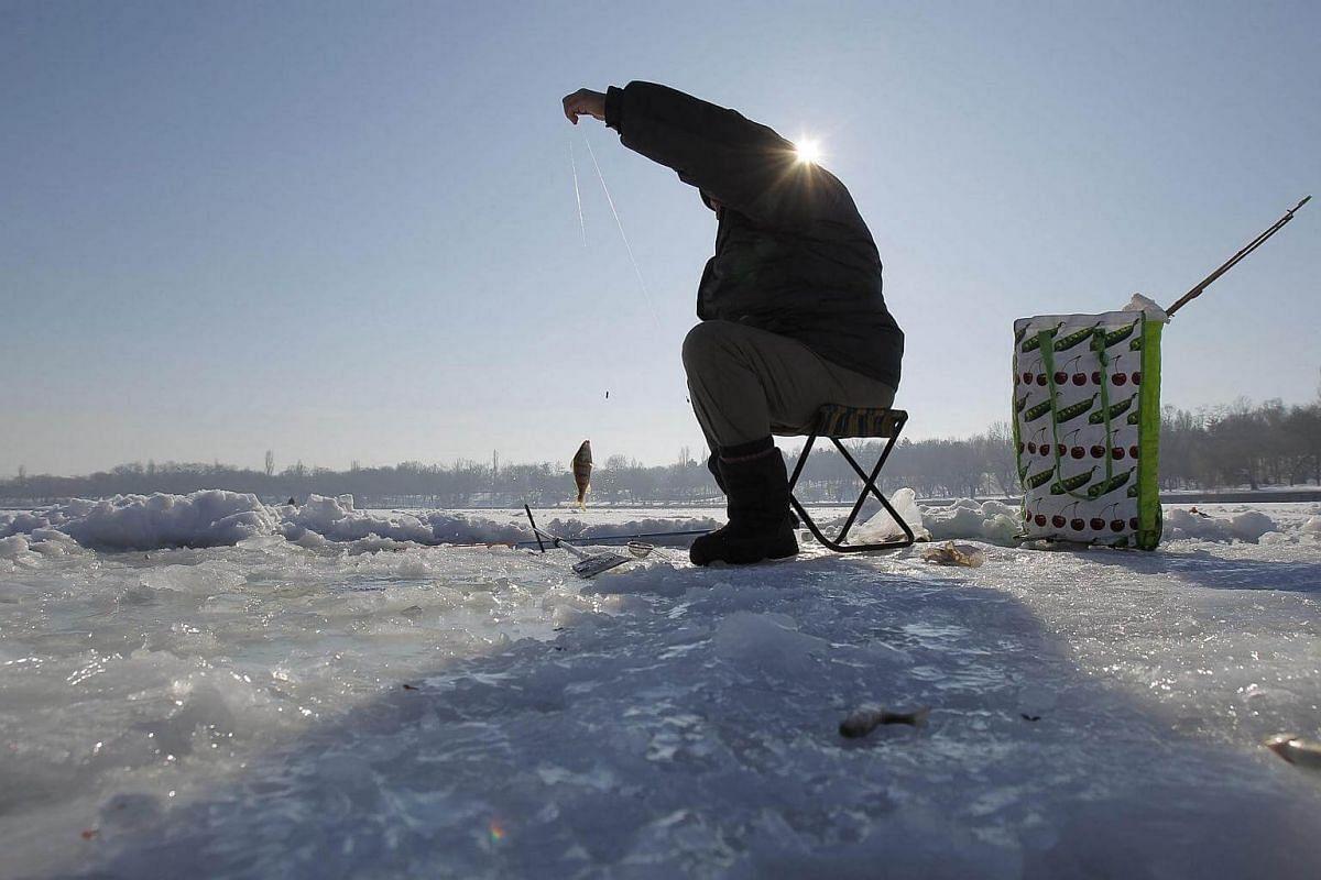 A man fishing on a frozen lake near Bucharest, Romania, on Jan 15, 2017.
