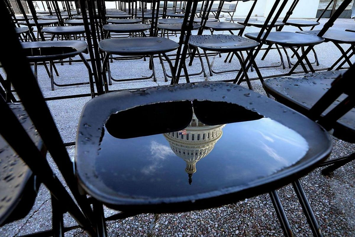 The US Capitol dome is reflected in water pooled in a folding chair that will used by spectators during a dress rehersal for the presidential inguration ceremony, on Jan 15, 2017, in Washington, DC.