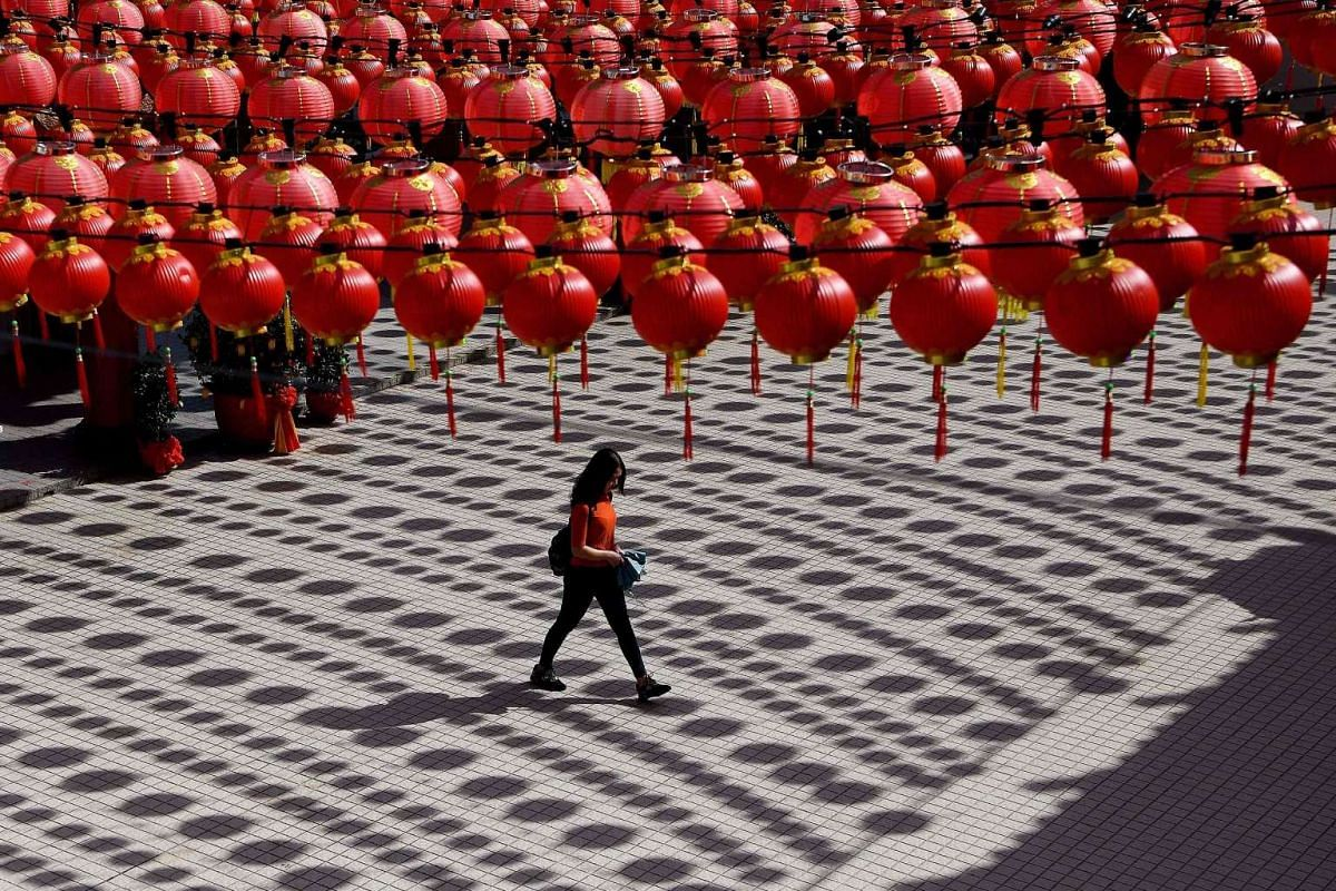 A woman walks under traditional Chinese lanterns decorated at the Thean Hou temple ahead of Lunar New Year of the rooster celebrations in Kuala Lumpur on Jan 17, 2017.