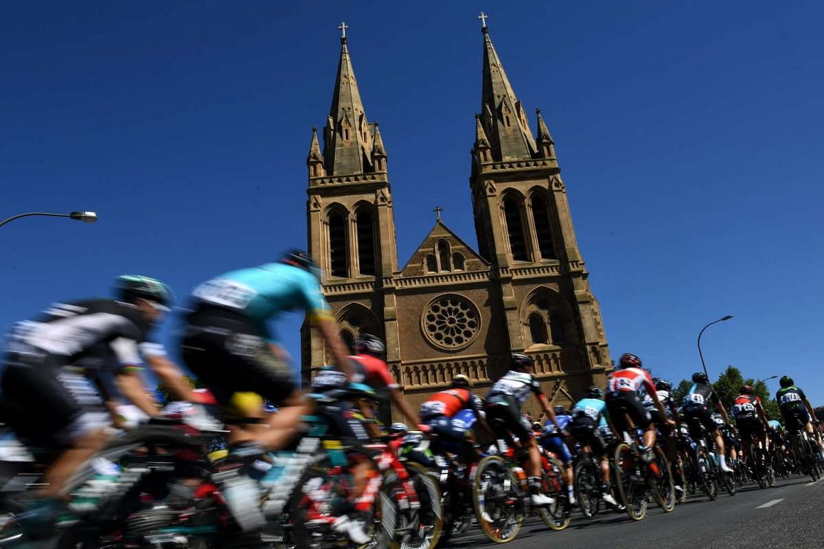 A peloton of cyclists rolls past St. Peter's Cathedral during stage one of the Tour Down Under in Adelaide on Jan 17, 2017.