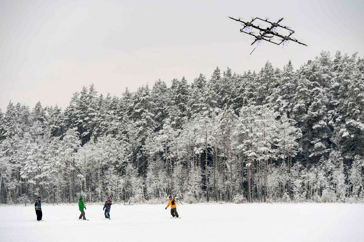 Snowboarders are pulled by a sixteen-propeller drone on Niniera lake surface near Cesis on Jan 14, 2017.