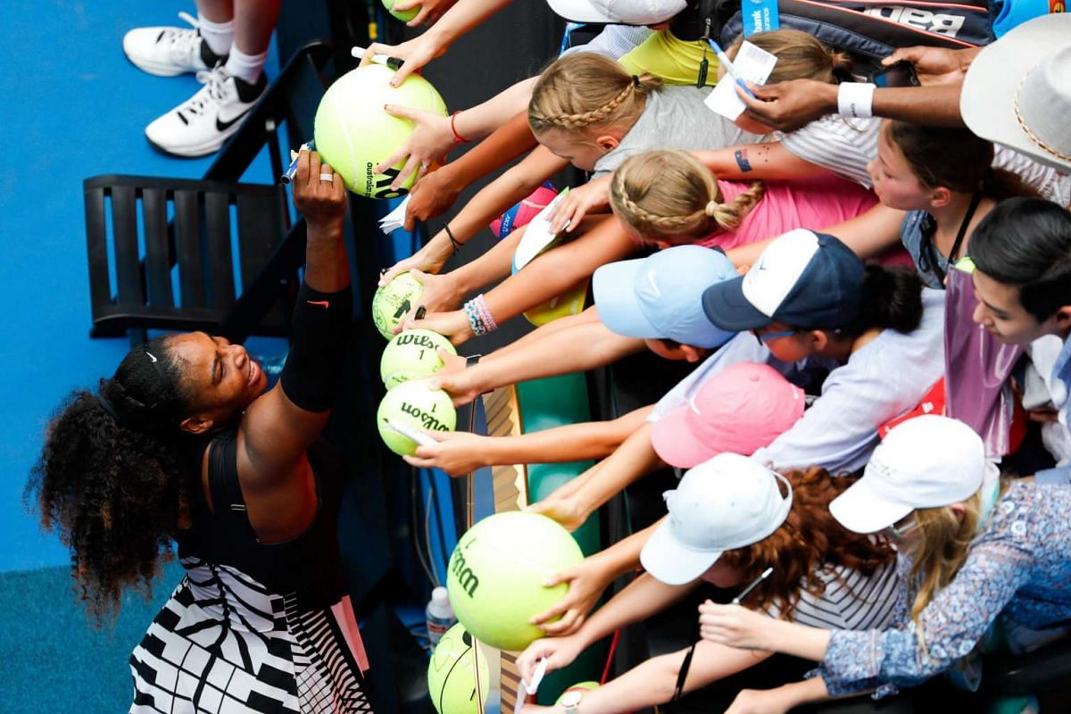 Serena Williams (left) of the USA signs autographs for fans after winning her Women's Singles first round match against Belinda Bencic of Switzerland at the Australian Open Grand Slam tennis tournament in Melbourne on Jan 17, 2017.