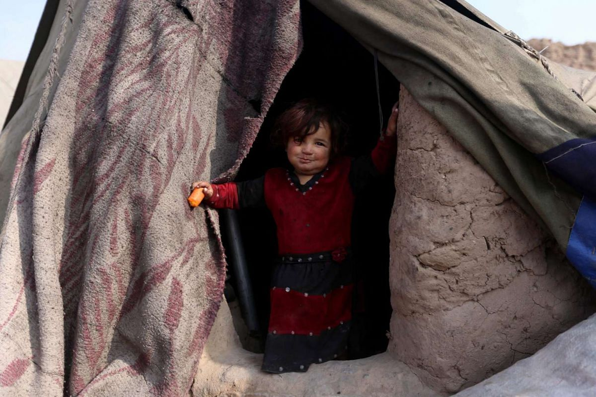 An internally displaced girl poses for a photograph at a temporary shelter in Enjil district of Herat province, Afghanistan on Jan 17, 2017.