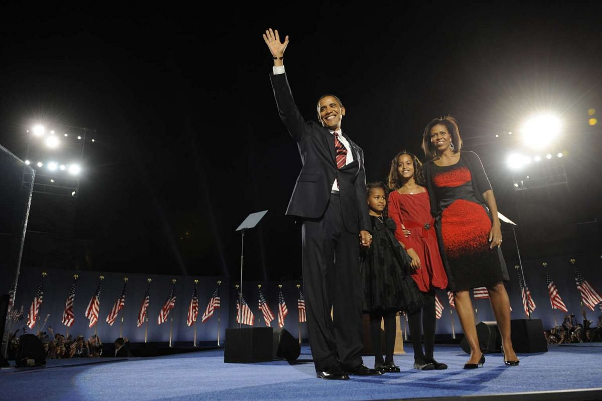 President-elect Barack Obama acknowledges the crowd flanked by wife Michelle and daughters Sasha and Malia following his victory speech at his election party in Chicago on Nov 4, 2008.