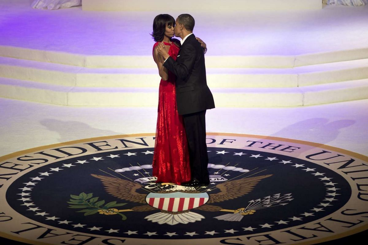 US President Barack Obama and First Lady Michelle Obama kiss while dancing at the Commander and Chief Ball at the Washington Convention Centre on Jan 21, 2013 in Washington, DC.
