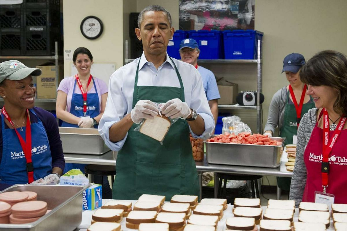 US President Barack Obama makes bologna sandwiches alongside Ms Dolly Garcia (right), a federal employee from the US Census Bureau, and Ms Chantelle Britton, a federal employee from the Department of Health and Human Services, at Martha's Table in Wa