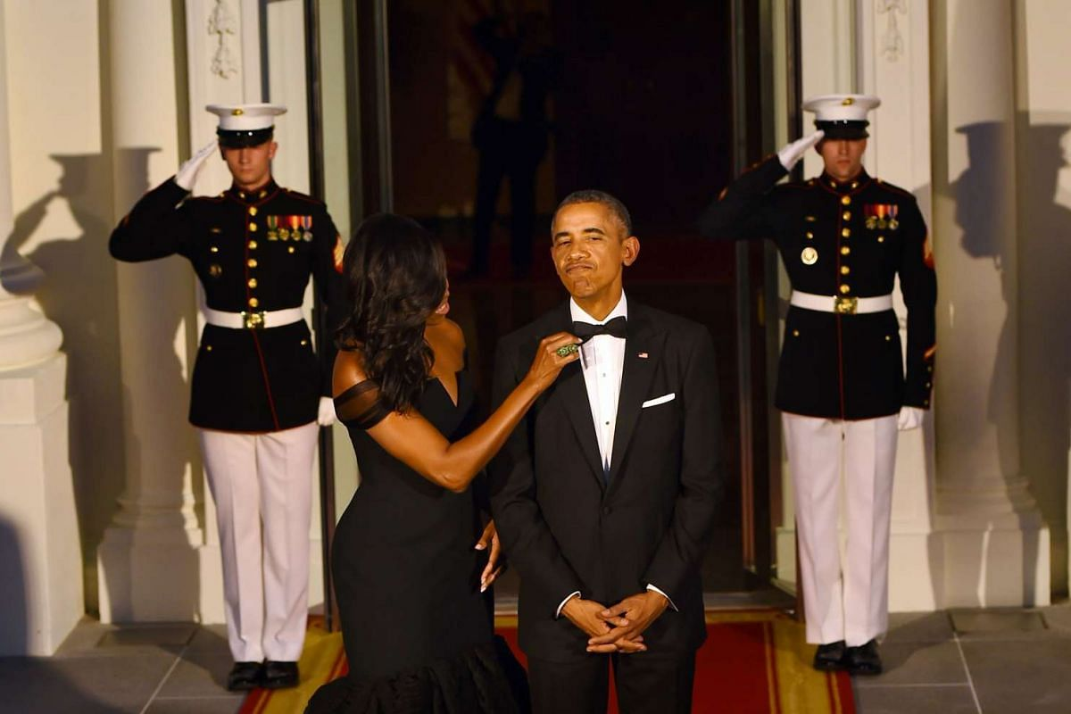 US President Barack Obama (right) has his tie adjusted by US First Lady Michelle Obama as they await the arrival of Chinese President Xi Jinping and his wife Peng Liyuan to the White House on Sept 25, 2015 in Washington, DC.