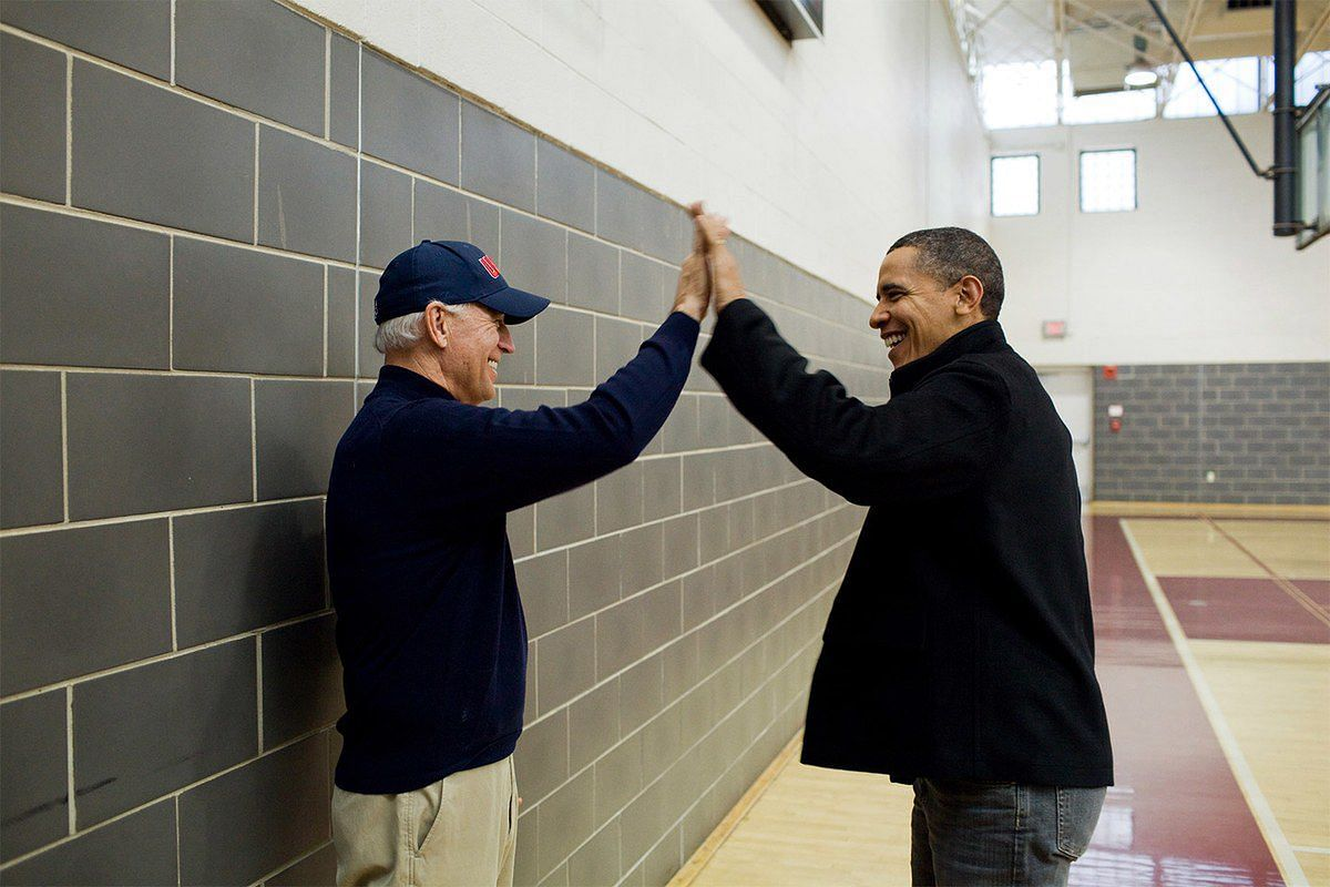 President Barack Obama and Vice-President Joe Biden high-five after watching Sasha Obama and Maisy Biden play in a basketball game in Chevy Chase, Maryland on Feb 27, 2010.