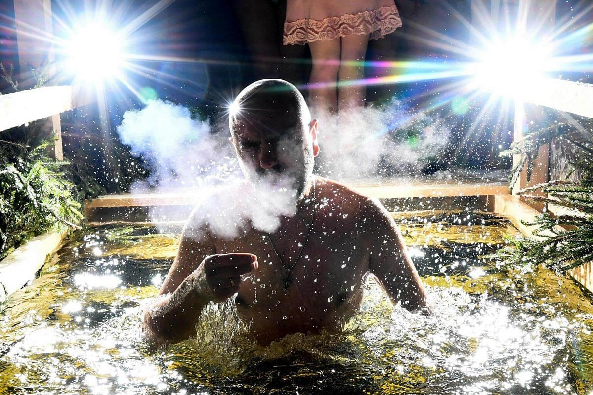 A Christian Orthodox believer plunges into the icy waters of a pond during the celebration of the Epiphany holiday in Moscow.