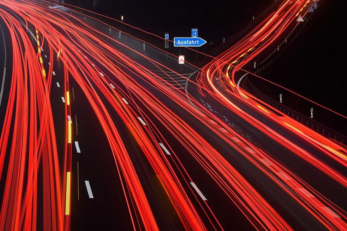 """Light traces of cars driving on the A2 highway at the exit """"Lehrte"""" near Hanover, central Germany."""