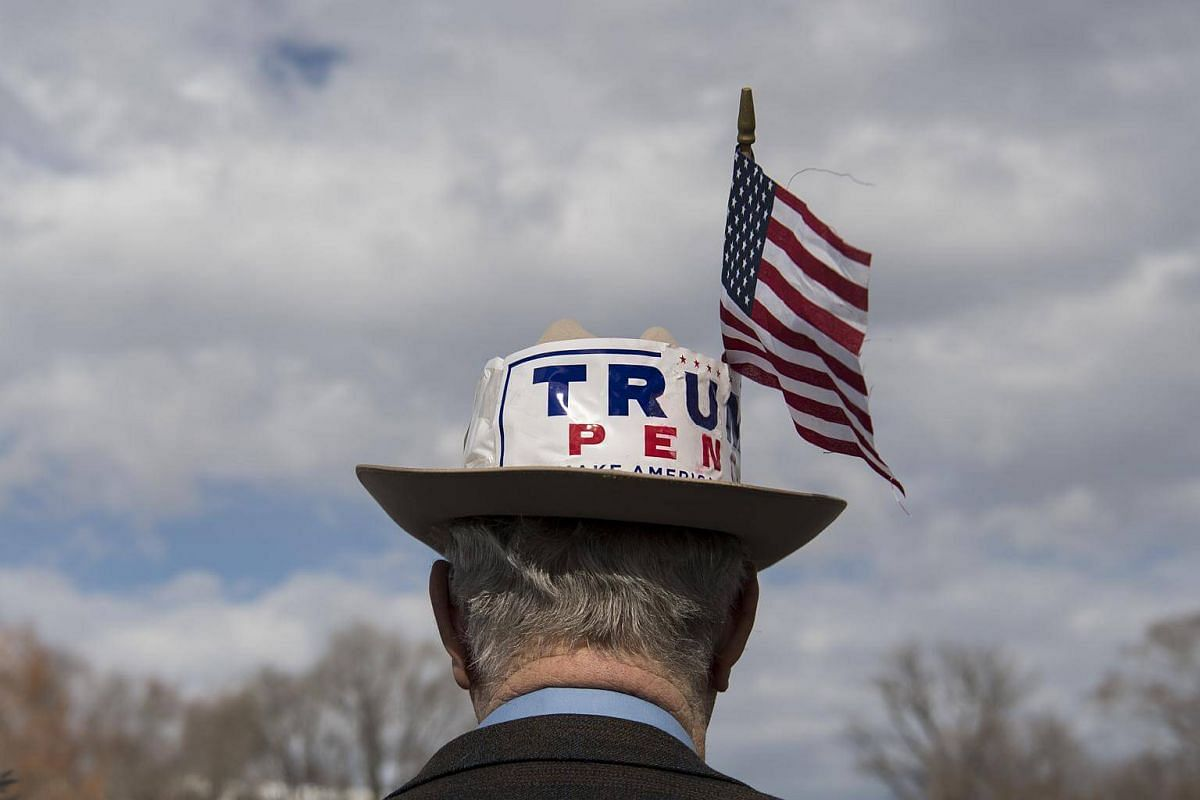 A visitor wears a hat displaying the names of US President-elect Donald Trump and US Vice President-elect Mike Pence with an American flag in front of the US Capitol in Washington, DC, on Jan 18, 2017.