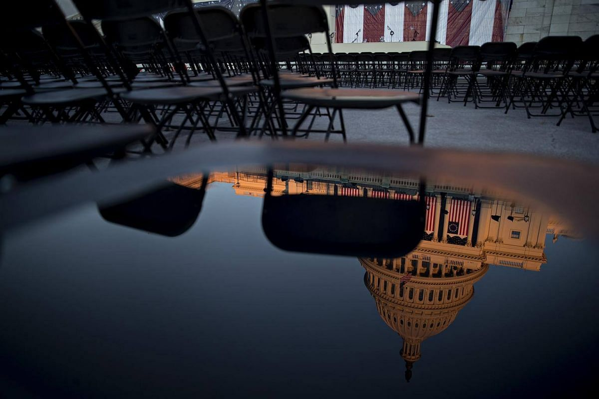 The US Capitol is reflected in a puddle on a chair at the West Front of the US Capitol in Washington, DC, on Jan 18, 2017.