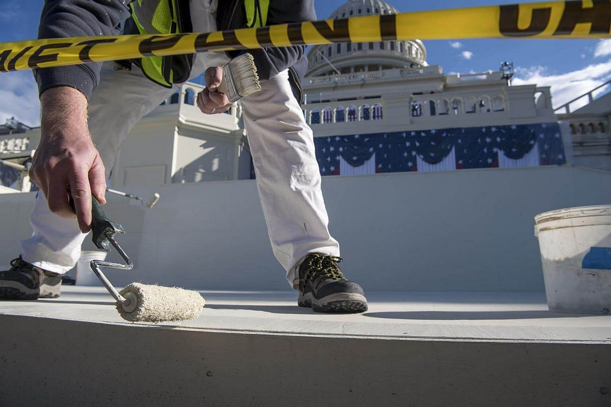 An Architect of the Capitol (AOC) employee paints a section of the floor of the inaugural platform on the West Front of the US Capitol in Washington, DC, on Jan 18, 2017.