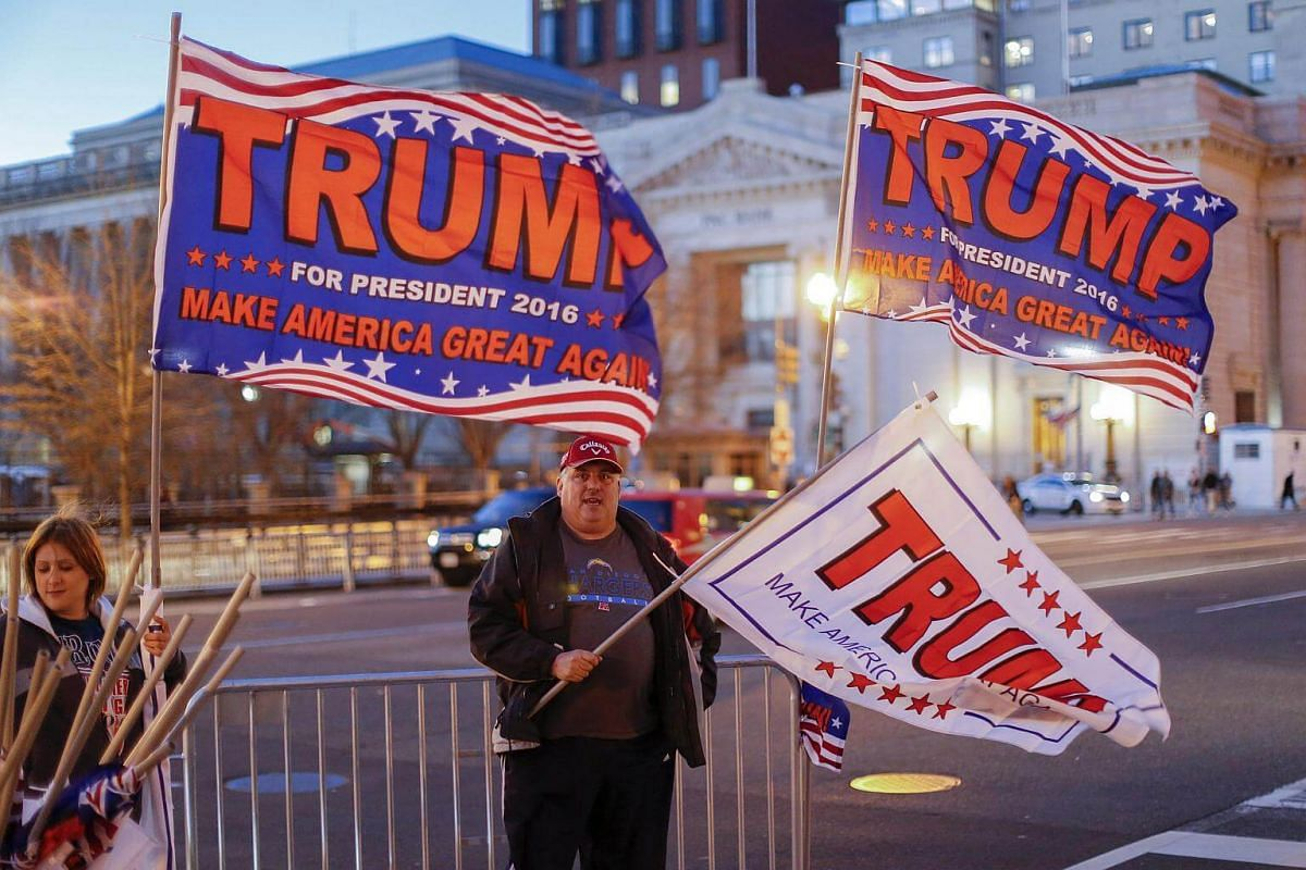 Amber Minney (left) and Phillip Farren of Buffalo, New York try to sell Donald Trump campaign flags, two days before Trump is sworn in as the 45th President of the United States in Washington, DC, on Jan 18, 2017.