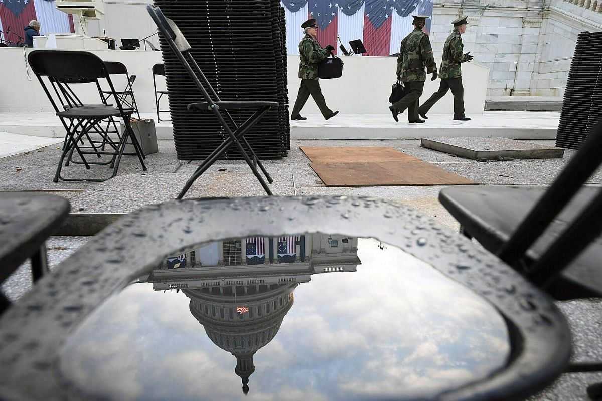 The US Capitol is reflected in a water puddle on a chair as people rehearse Sunday for Donald Trump's inauguration.