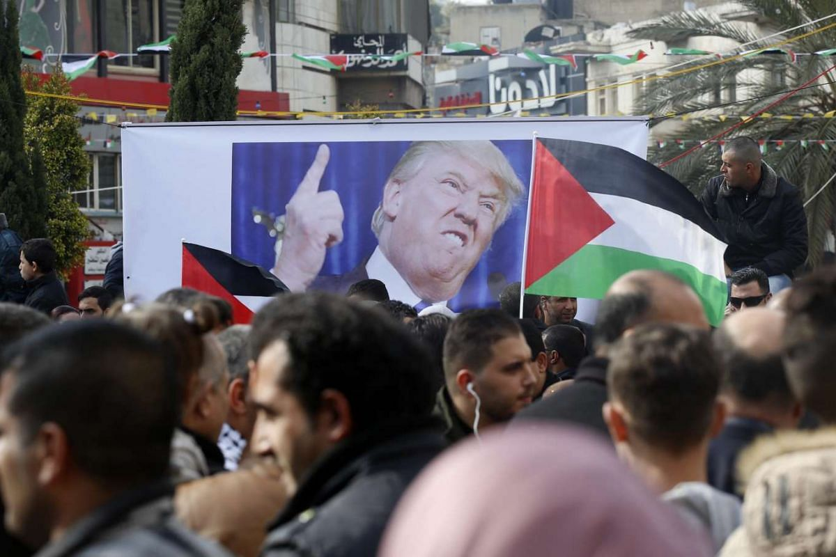 Palestinians protesting next to an image of Trump during a demonstration in the west bank City of  Nablus, against Trump's intention to move the US Embassy to Jerusalem.