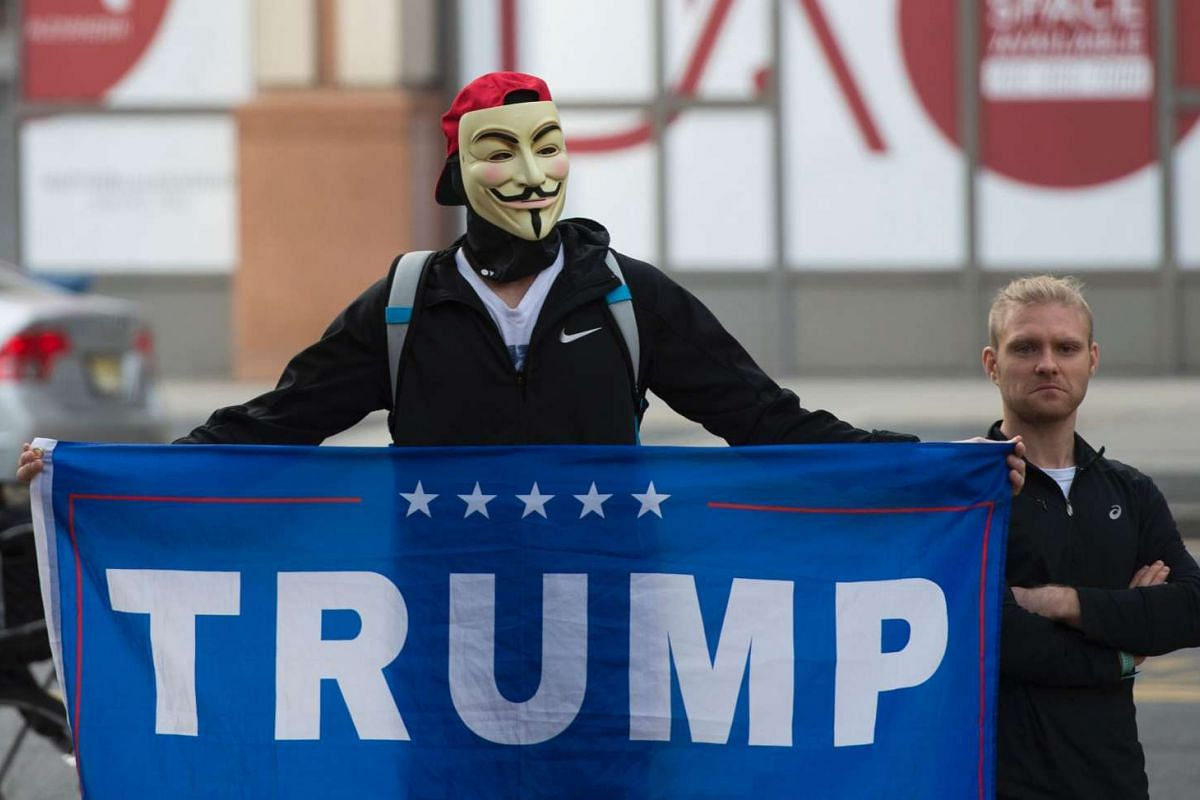Trump supporters holding up a sign near anti-Trump protesters close to the Hilton Garden Hotel in Washington DC on Jan 19, 2017.