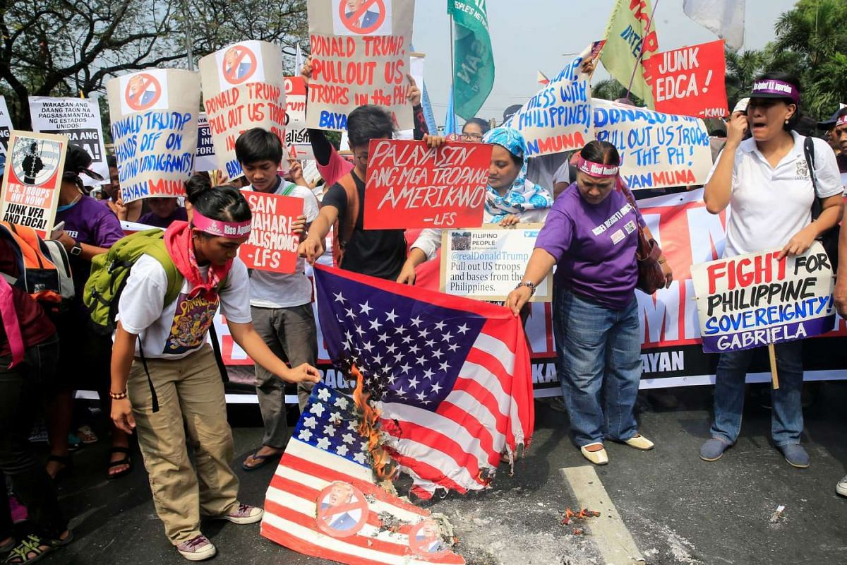 Protesters burning a US flag and a mock flag with pictures of Trump outside the US embassy in Manila, the Philippines, on Jan 20, 2017.