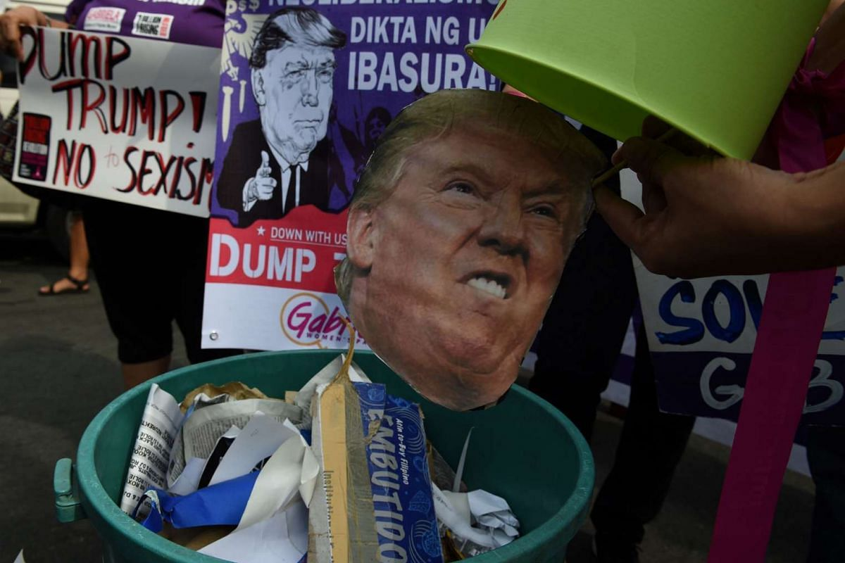 Activists dump a photo of US President-elect Donald Trump into a trash bin in a symbolic gesture during a rally in front of the US embassy in Manila, the Philippines, on Jan 20, 2017.