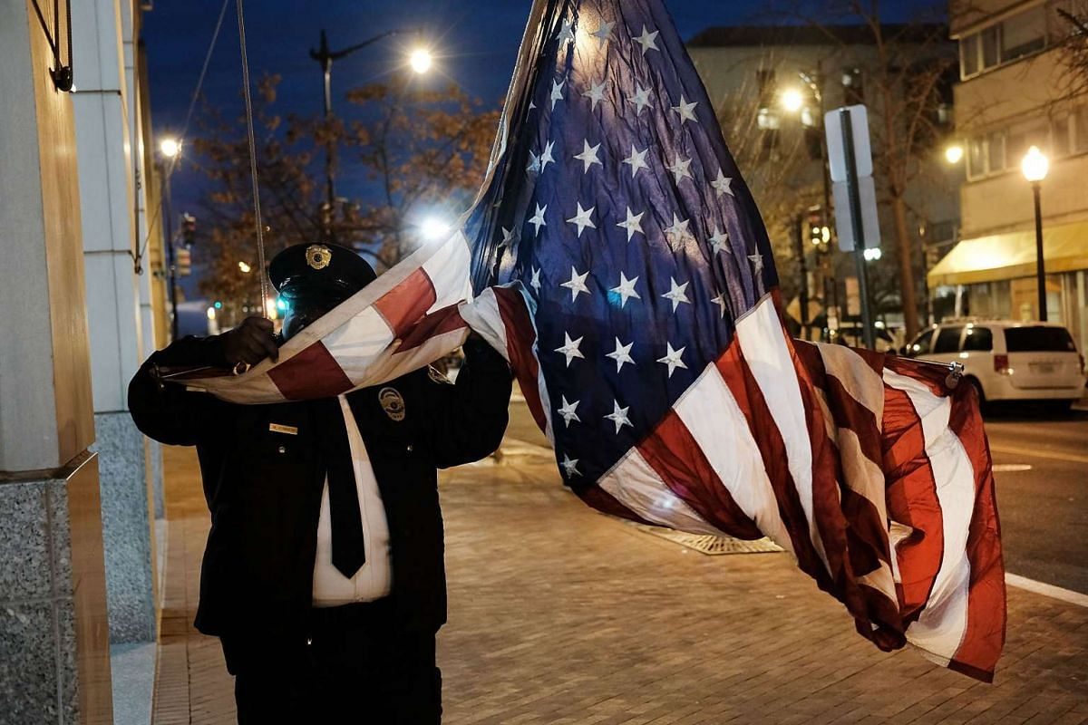 A building security guard raises the American flag on the morning of the inauguration on Jan 20, 2017 in Washington, DC.
