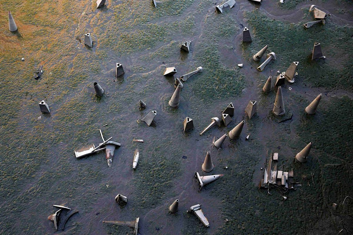 Traffic cones are seen on the bank of the River Thames during low tide in London, Britain.
