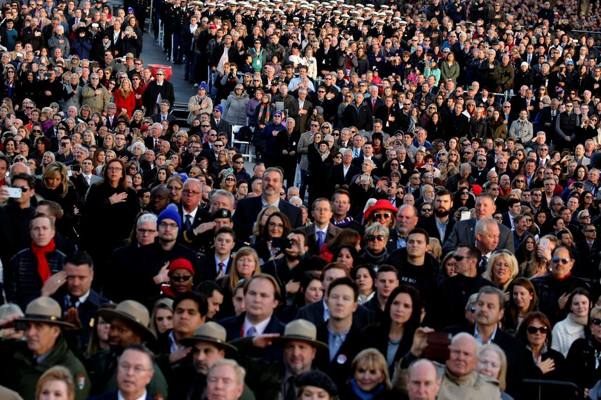 People stand for the national anthem before US President-elect Donald Trump arrives at a Make America Great Again welcome concert in Washington on Jan 19, 2017.