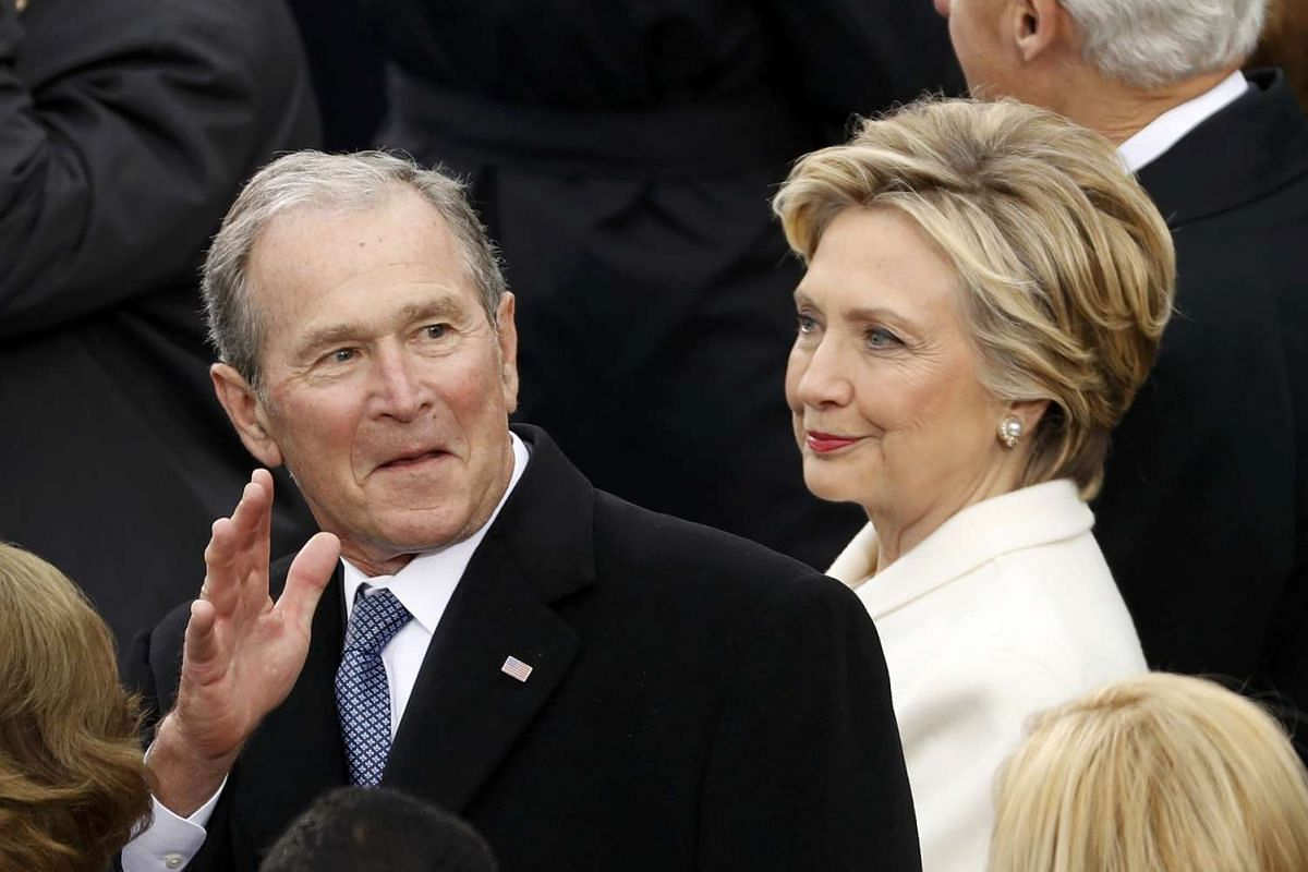 Former US president George W. Bush, seated beside Mrs Clinton, waves to the crowd.