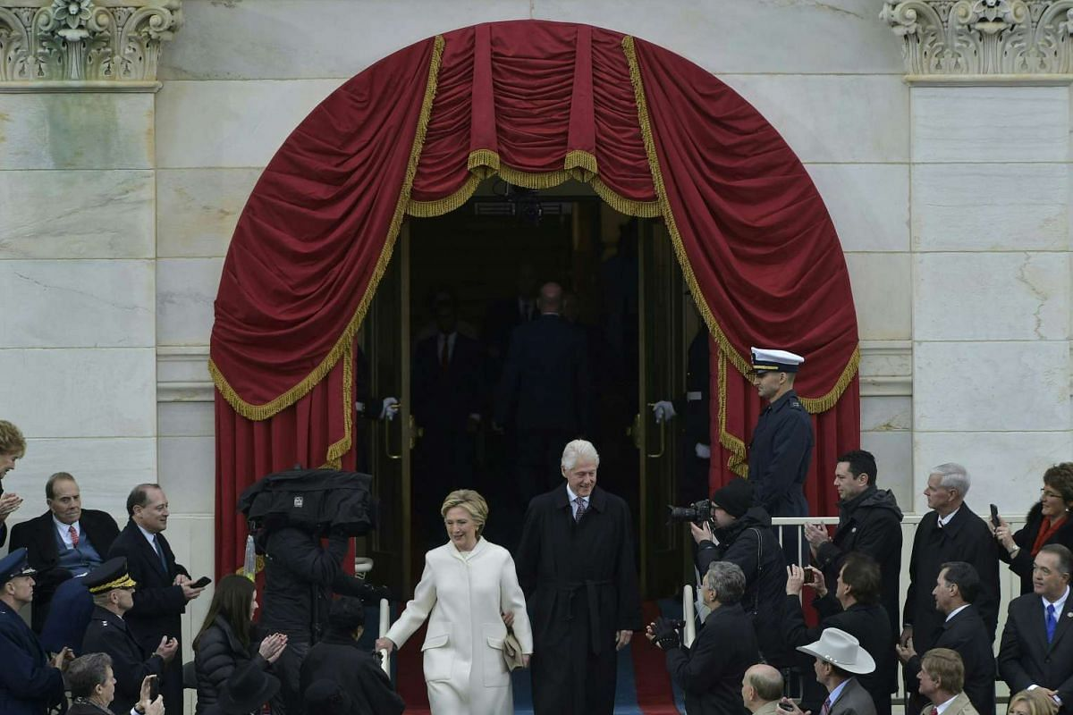 Mrs Clinton arrives at the inauguration of Mr Trump with her husband Bill at Capitol on Friday (Jan 20).
