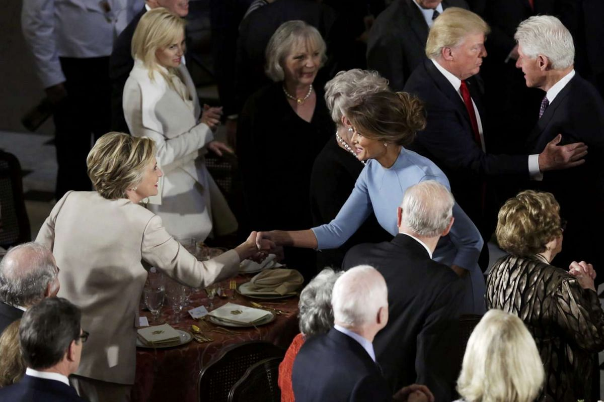 Mrs Clinton greets First Lady Melania Trump as their husbands exchange words during the Inaugural luncheon at the National Statuary Hall in Washington, DC.