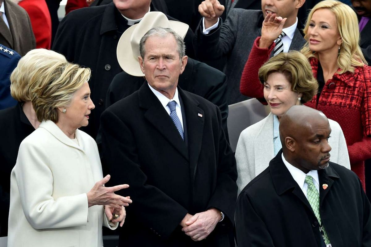 The former US secretary of state speaks to Mr Bush and his wife Laura before the presidential inauguration.