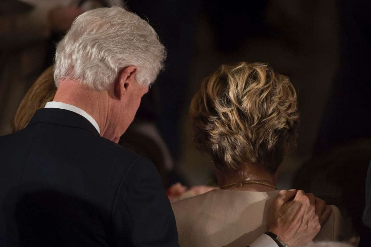 The Clintons bow their heads in prayer during the Inaugural Luncheon following the inauguration.