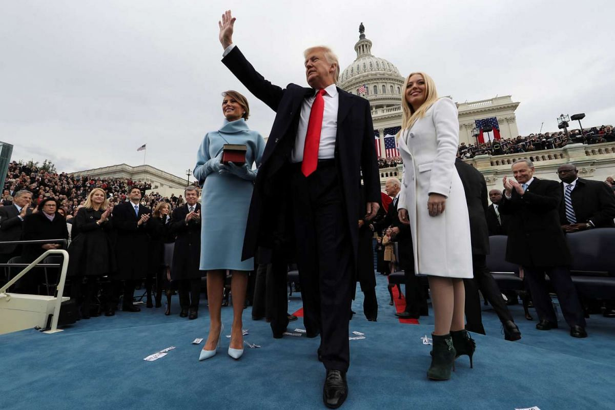US President Donald Trump acknowledges the audience after taking the oath of office as his wife Melania (left) and daughter Tiffany watch on Jan 20, 2017.