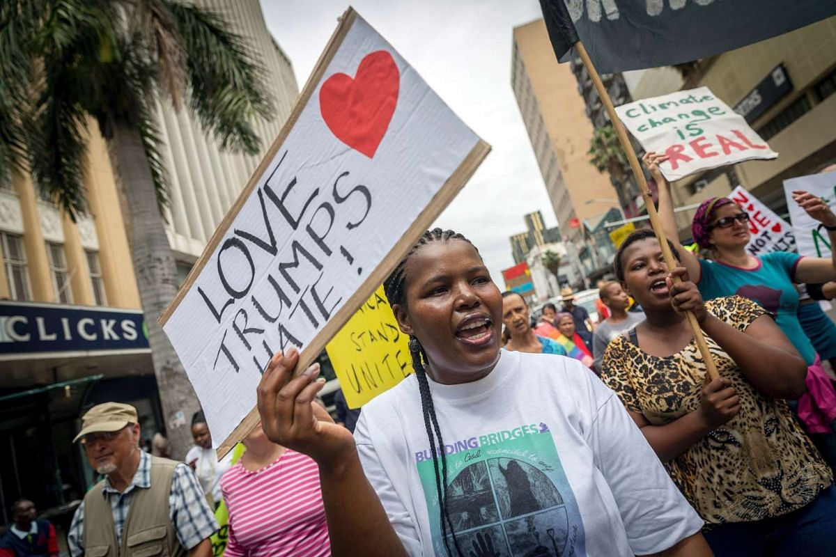 Anti-Trump protesters shout slogans and hold placards against the newly sworn US president Donald Trump during a demonstration organised by Earthlife Africa in the central streets of Durban following his inauguration on Jan 21, 2017 in Durban, South