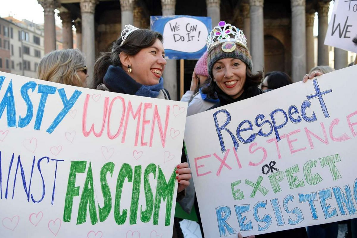 Two women hold signs during a rally against US newly sworn-in President Donald Trump in Rome on Jan 21, 2017, a day after Trump's inauguration.