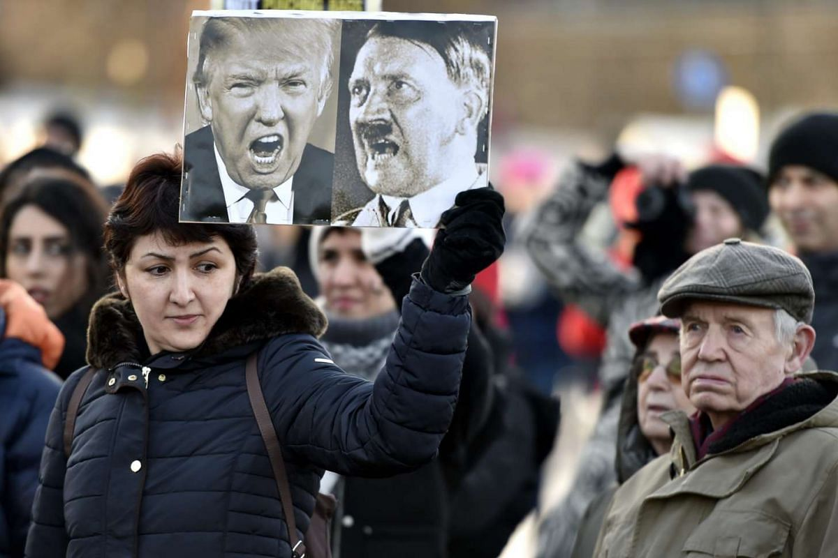 A participant of a Women's March in Helsinki holds up a poster depicting US President Donald Trump and German dictator Adolf Hitler on Jan 21, 2017, one day after the US president's inauguration.