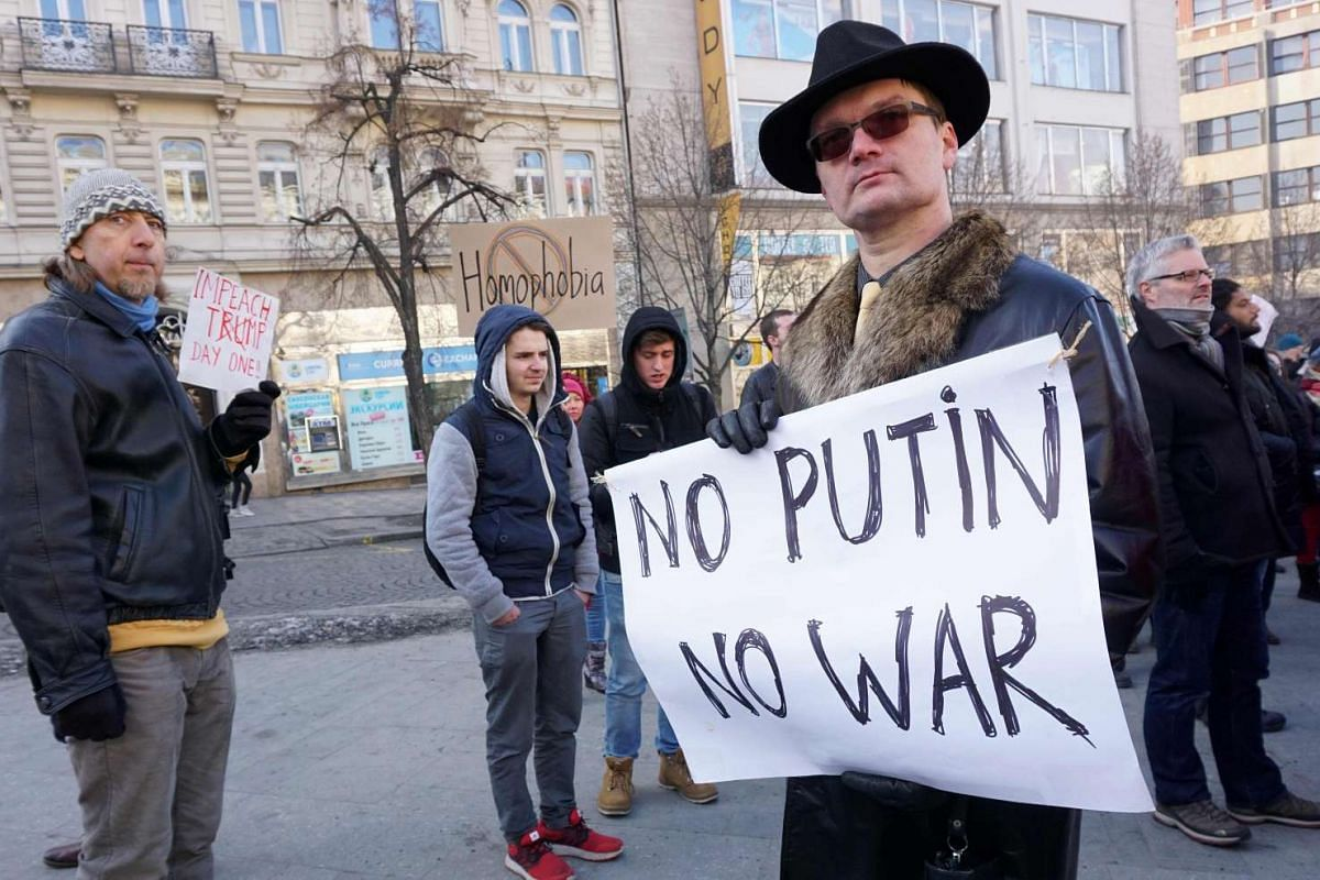 """A man holds a poster reading """"No Putin No War"""" as another one pleads for the impeachment of US President Donald Trump during a rally in solidarity with supporters of the Women's March taking place in Washington and many other cities on Jan 21, 2017 i"""