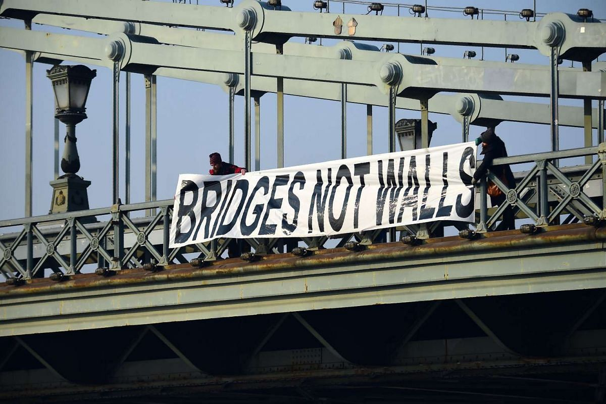 """Participants hold a banner """"Bridges not walls"""" on Lanchid (Chain Bridge) in Budapest, Hungary, on Jan 21, 2017 during a women protesters march in a rally against US President Donald Trump following his inauguration."""