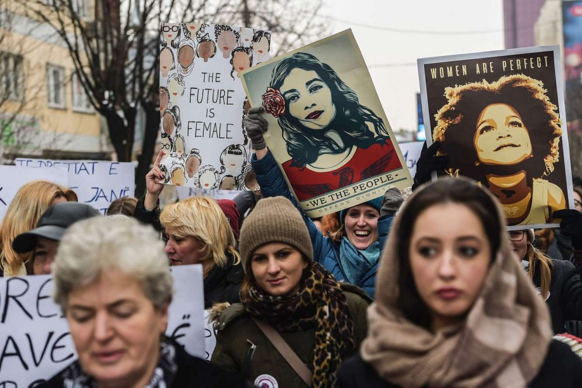 Women hold posters as they take part in a march for women's rights and freedom in solidarity with the march organised in Washington, on Jan 21, 2017 in Pristina, Kosovo.