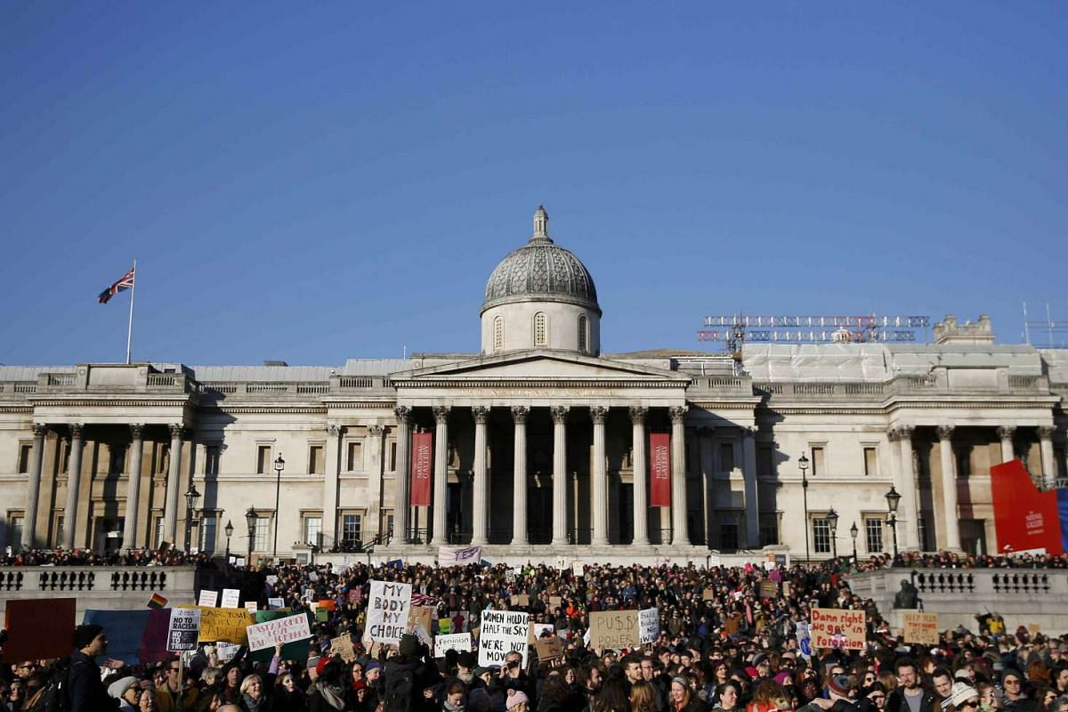 Protesters carrying banners take part in the Women's March on London, as they stand in Trafalgar Square, in central London, Britain Jan 21, 2017.