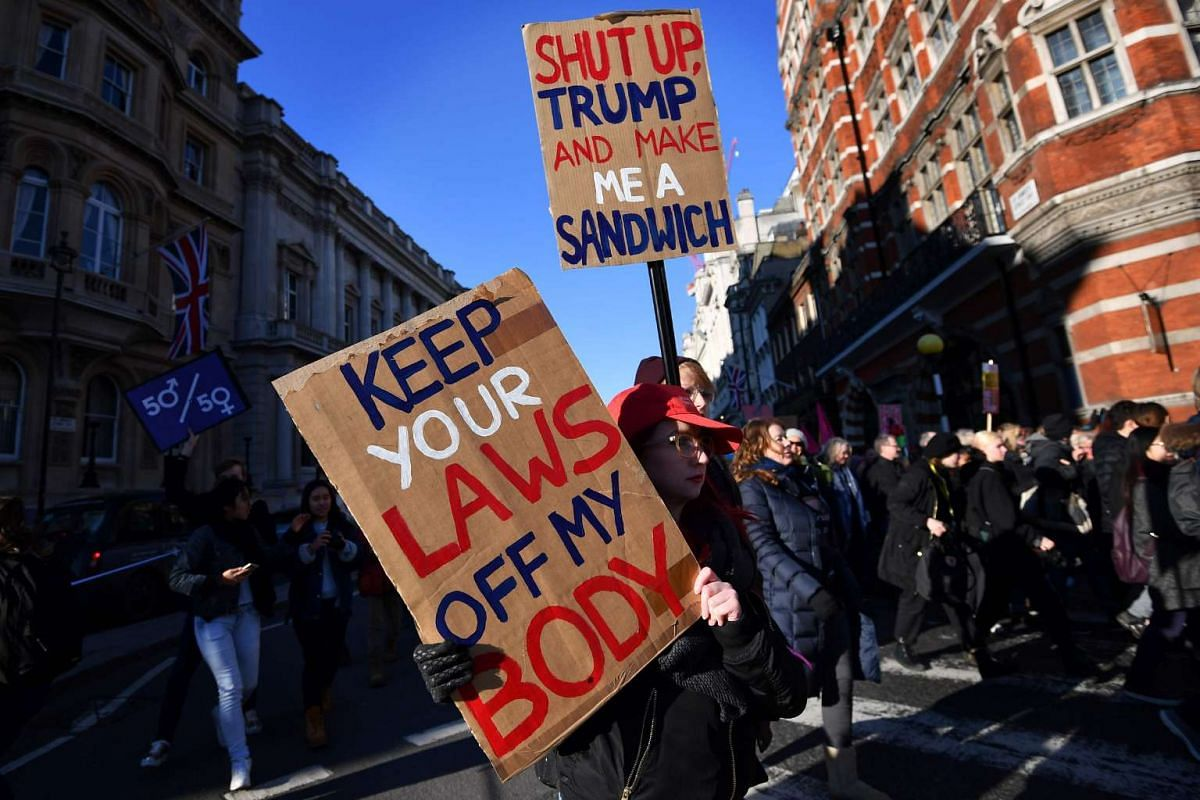 Protesters hold placards during the Women's March in London on Jan 21, 2017 as part of a global day of protests against new US President Donald Trump.