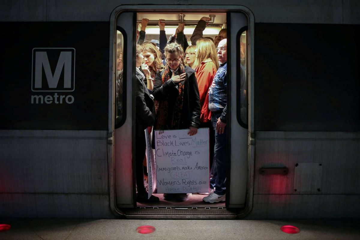 A woman activist holding a placard is seen on a Metrorail as they make their way to the Women's March in opposition to the agenda and rhetoric of President Donald Trump in Washington, D.C., U.S. on January 21, 2017. PHOTO: REUTERS