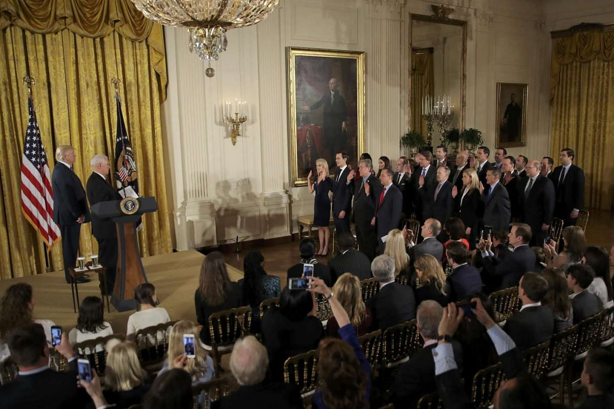 U.S. President Donald Trump (L) watches as Vice President Mike Pence swears in senior staff at the White House in Washington, DC January 22, 2017. PHOTO: REUTERS