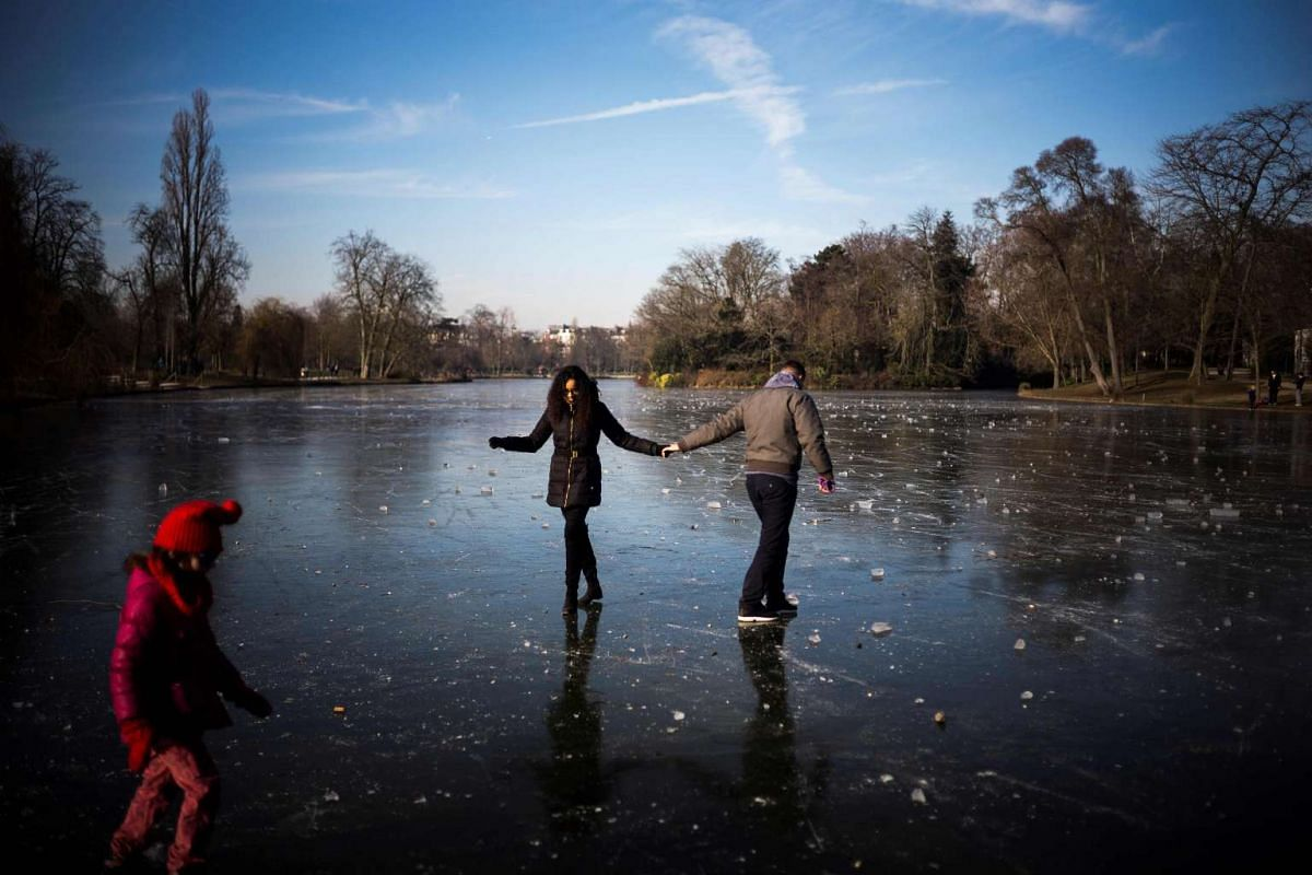 People enjoy the ice on the frozen Daumesnil lake at the Bois de Vincennes park in Paris on January 22, 2017. PHOTO: AFP