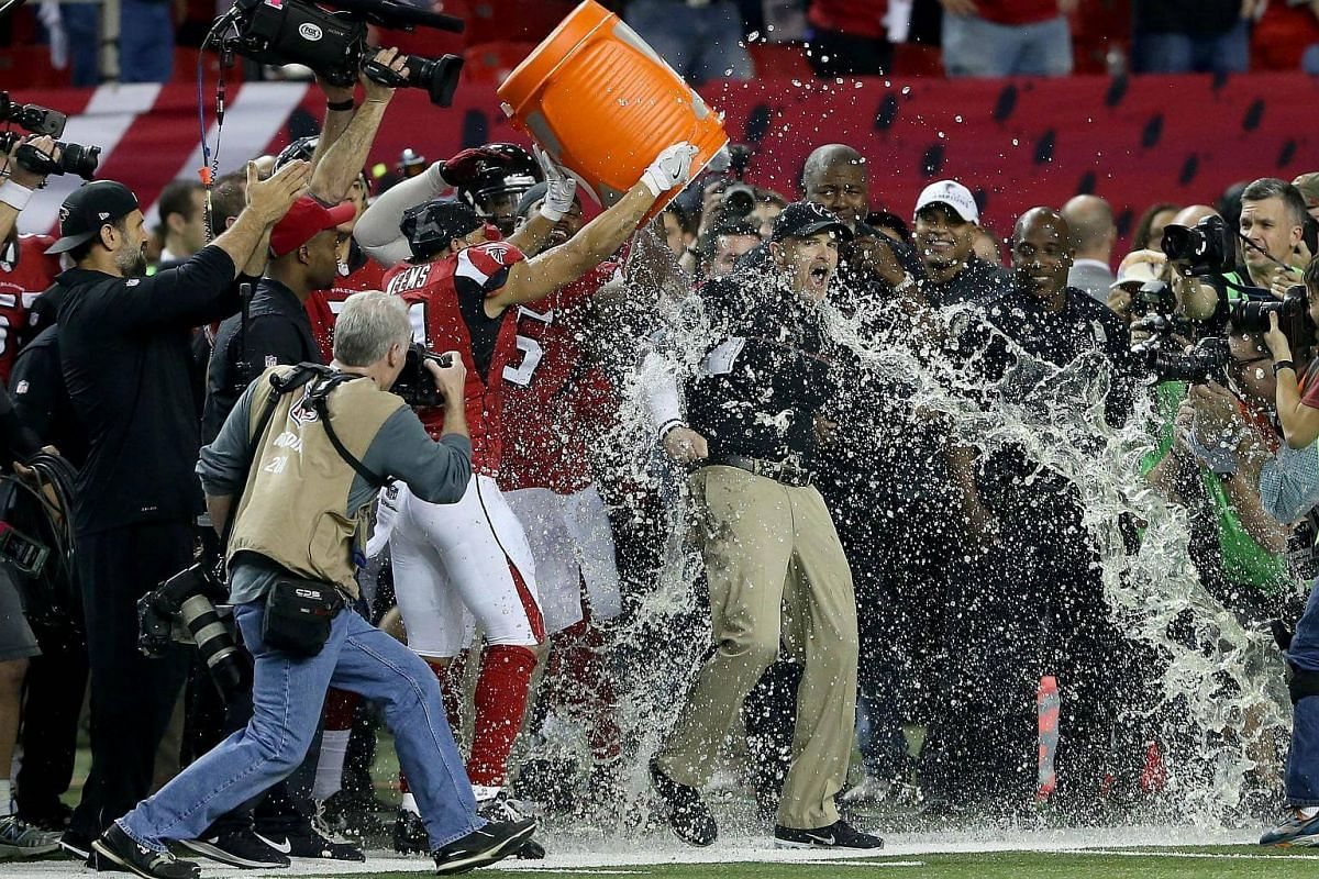 Head coach Dan Quinn of the Atlanta Falcons has Gatorade dumped on him by his team late in the game against the Green Bay Packers in the NFC Championship Game at the Georgia Dome on Jan 22, 2017, in Atlanta, Georgia.