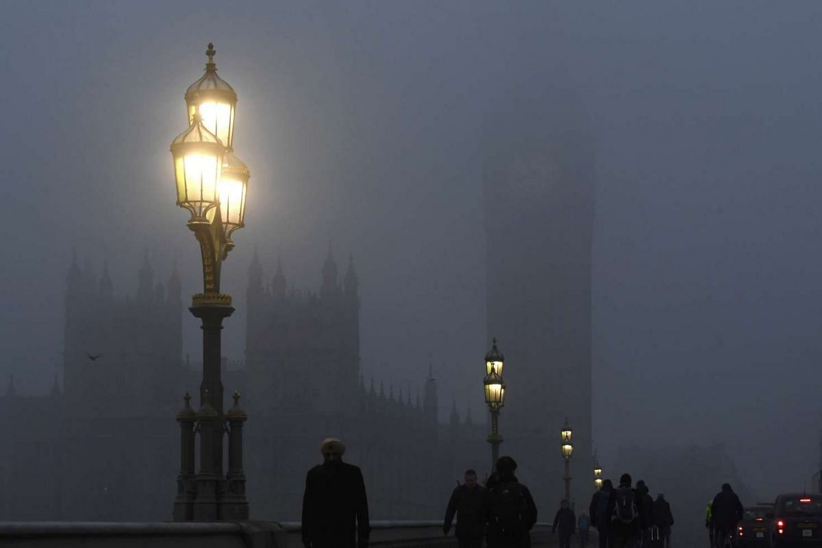 People walking across Westminster Bridge in front of the Houses of Parliament.