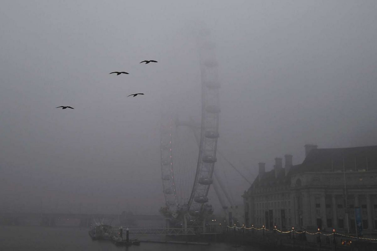 The London Eye is hardly visible during a foggy morning in London.