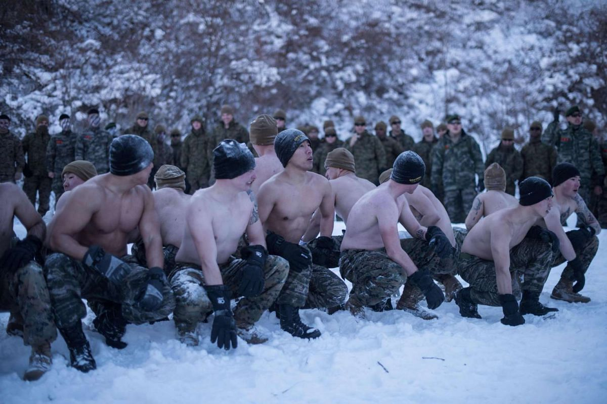 South Korean and US soldiers preparing to throw snow on themselves as they perform a demonstration for the media during a joint annual winter exercise in Pyeongchang, on Jan 24, 2017.