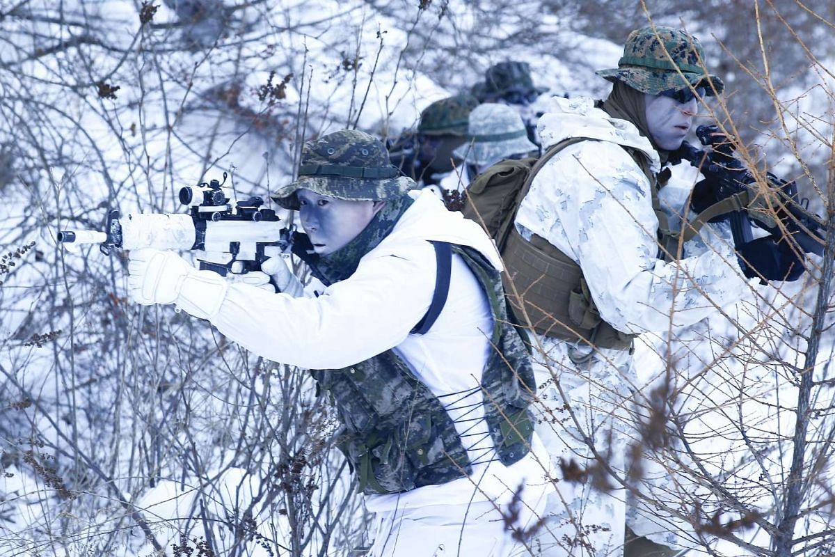 US Marines and South Korean Marine Corps soldiers taking up positions in a snowy field during a winter exercise in Pyeongchang, on Jan 24, 2017.