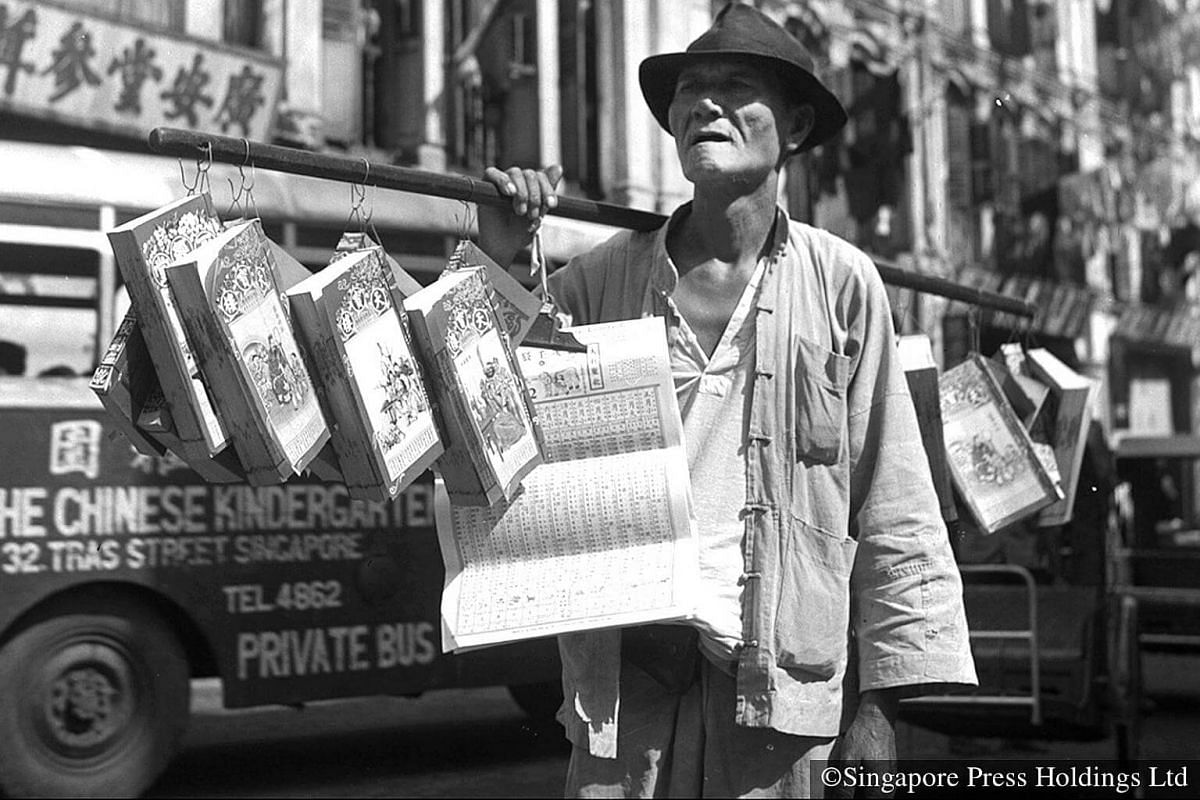 1952: A peddler selling the Chinese Almanac, a traditionally auspicious item for the Chinese New Year, on a Chinatown street.
